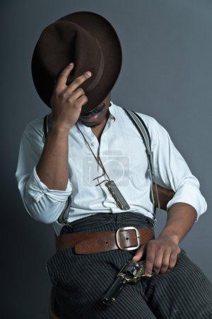 Photo pour Sommeil homme afro rétro de cowboy western d'Amérique avec moustache. assis sur une chaise en bois. tenant un pistolet. porter un chapeau brun. cool gars dur. - image libre de droit