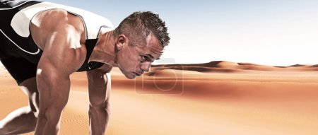 Extreme athlete runner man in starting position outdoor in desert on hot summer day.
