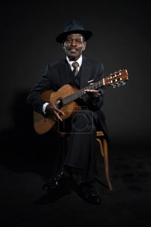 Photo for Retro senior afro american blues man. Wearing striped suit with blue hat. Playing acoustic guitar. - Royalty Free Image