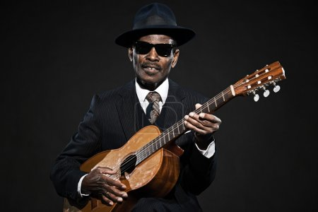 Photo for Retro senior afro american blues man. Wearing striped suit with blue hat and black sunglasses. Playing acoustic guitar. - Royalty Free Image