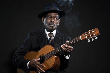 Photo for Retro senior afro american blues man. Wearing striped suit with blue hat. Playing acoustic guitar. Smoking cigar. - Royalty Free Image