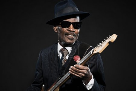 Photo for Retro senior afro american blues man. Wearing striped suit with blue hat and black sunglasses. Playing electric guitar. - Royalty Free Image