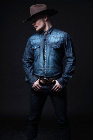 Photo pour Cowboy de la mode moderne. porter le chapeau brun et bleu jeans chemise. blonde cheveux et la barbe. Studio tourné contre black. - image libre de droit