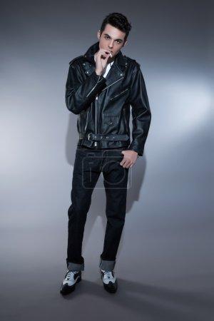 Retro rock and roll 50s fashion man with dark grease hair. Smoki