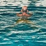 Healthy senior man with beard in indoor swimming p...
