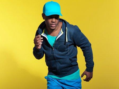 Photo pour Athlétique coureur vêtu de bleu sportswear fashion. homme noir. Casquette bleue et chandail. couleurs intenses. Studio tourné sur fond jaune. - image libre de droit