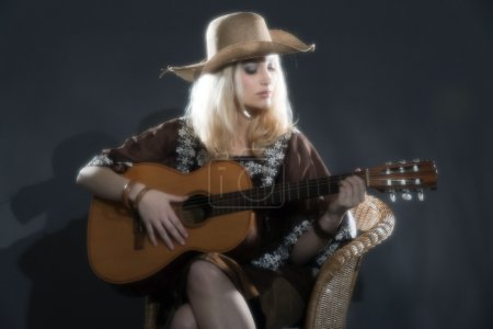 Retro soft focus hippie 70s country guitar girl with long blonde
