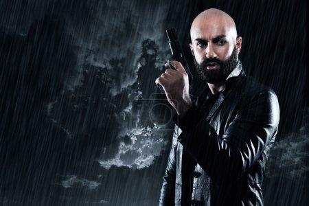 Dangerous bald gangster man with beard holding gun...