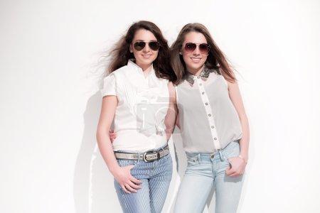 Foto de Dos verano casual moda morenas chicas con cabello largo contra la pared blanca. lleva gafas de sol. cara sonriente. - Imagen libre de derechos