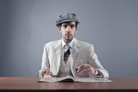 Mafia fashion man wearing white striped suit and cap. Sitting at