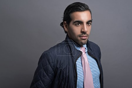 Photo for Contemporary fashion man wearing blue jacket and pink tie. Black hair and brown skin. Studio shot against grey. - Royalty Free Image