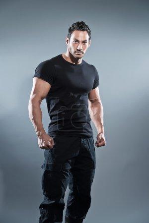 Photo pour Homme de fitness musclé de combat portant chemise et pantalon noirs. Studio tourné contre gris . - image libre de droit
