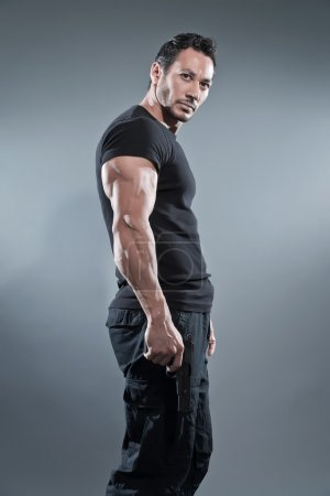 Action hero muscled man holding a gun. Wearing black t-shirt and