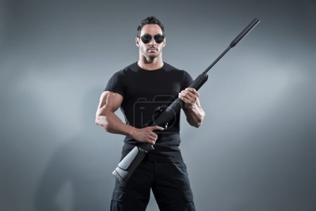 Photo for Action hero muscled man holding a rifle. Wearing black t-shirt with pants and sunglasses. Studio shot against grey. - Royalty Free Image