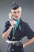 Calling retro blonde stewardess wearing blue suit. Holding white
