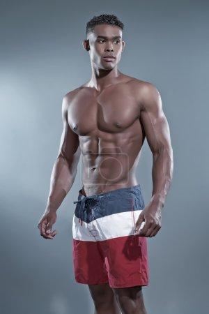 Photo for Fitness black african man wearing striped shorts. Swimwear fashion. Studio shot against grey. - Royalty Free Image