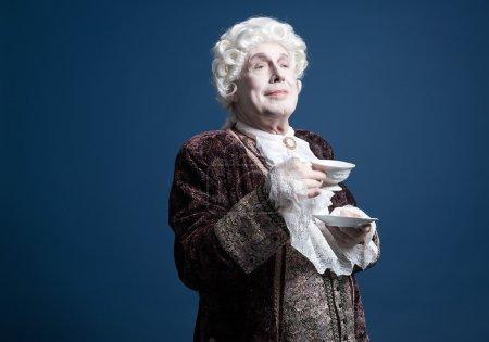 Smiling retro baroque man with white wig holding a porcelain tea
