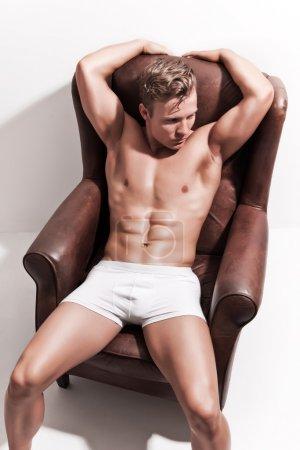 Photo pour Modèle de sous-vêtements masculins de musclé en short blanc. cheveux blonds. assis dans le fauteuil en cuir contre le mur blanc. - image libre de droit