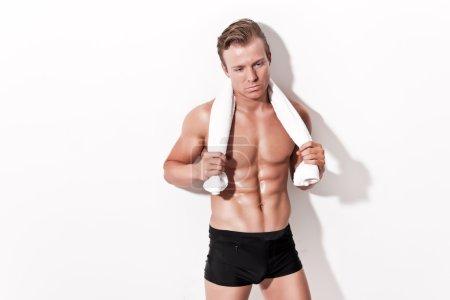 Male muscled underwear model wearing black shorts. Holding white