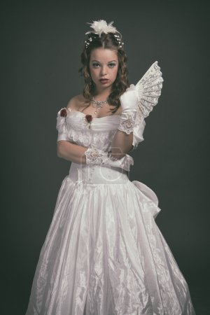 Victorian fashion woman wearing white dress. Holding fan. Studio