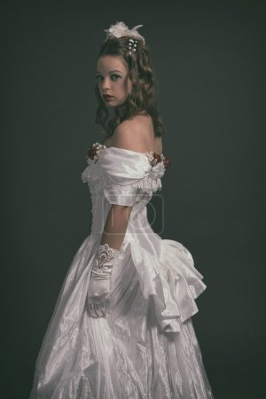 Victorian fashion woman wearing white dress. Studio shot against