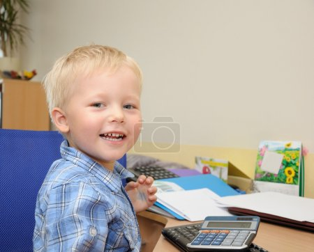 Cute boy in office with calculator