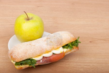 Real sandwich with smoked salmon, eggs and green with apple on a wooden background.