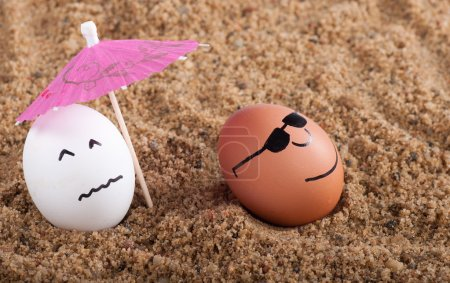 easter funny eggs under umbrella on a sand
