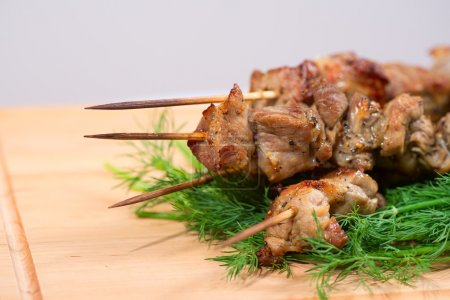 grill meat on a sticks with green on wooden plate