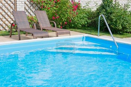 Photo pour Piscine avec eau bleue par une journée ensoleillée. Espace de loisirs avec un fragment de jardin et mobilier d'extérieur . - image libre de droit