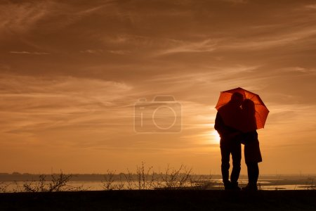 Silhouette of pregnant woman and a man in the sunset under an um