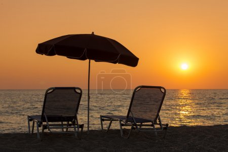 Beautiful beach with deck chairs and parasol at sunset