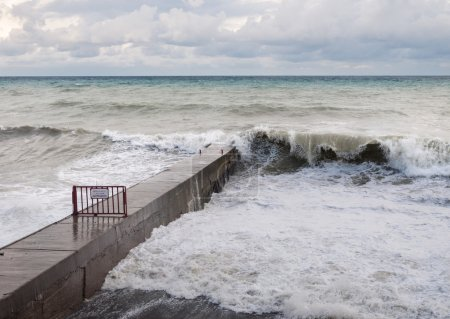 Photo for Storm waves roll on the concrete breakwater - Royalty Free Image