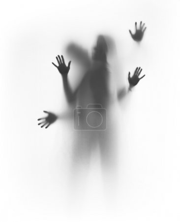 Diffuse silhouette of a couple behind a curtain. Faded shapes and hands.