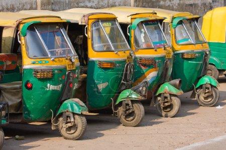 Photo pour Agra, Inde - 26 novembre : Auto rickshaw taxis sur une route à 26 novembre 2012 à Agra (Inde). Ces taxis emblématiques ont récemment été équipées d'un moteur GNV dans un effort pour réduire la pollution - image libre de droit