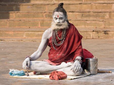 Photo pour VARANASI, INDE - 1er DÉCEMBRE : Un sadhu non identifié est assis sur le ghat le long du Gange le 1er décembre 2012 à Varanasi, en Inde. Le tourisme a attiré de nombreux prétendus faux sadhus à Varanasi - image libre de droit