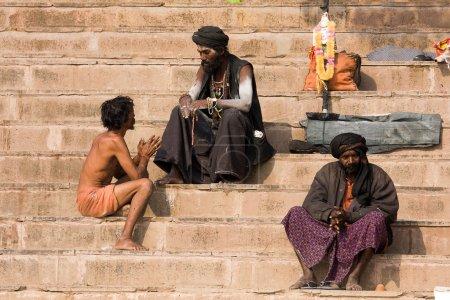 Photo pour VARANASI, INDE - 1er DÉCEMBRE : Un sadhu et un homme non identifiés sont assis sur le ghat le long du Gange le 1er décembre 2012 à Varanasi, en Inde. Le tourisme a attiré de nombreux prétendus faux sadhus à Varanasi - image libre de droit