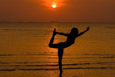 Photo pour Silhouette de femmes de yoga, travaillant sur des poses au coucher du soleil - image libre de droit