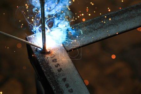 Photo pour Travailleur avec le métal et les étincelles de soudage avec des étincelles de soudage - image libre de droit