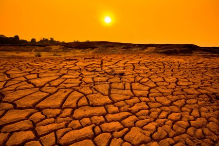 Photo for Sunset over cracked land and arid terrain - Royalty Free Image