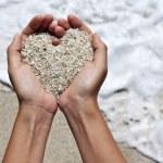 Mellow heart shaping female hands above beach...