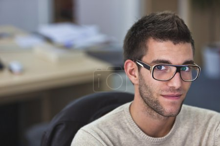Photo for Portrait of a smart an handsome young man in office with available light - Royalty Free Image