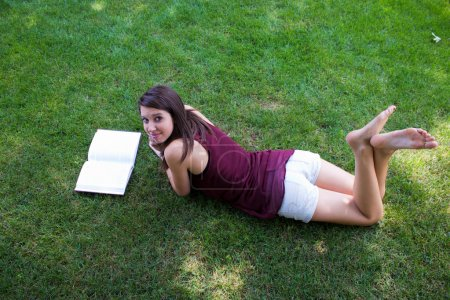Photo for A pretty girl reads a book in her backyard. - Royalty Free Image