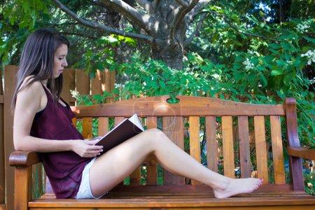 Photo pour Jolie adolescente lisant dehors sur un banc - copyspace - image libre de droit