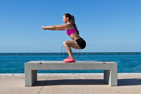 Hispanic woman doing squats by the water