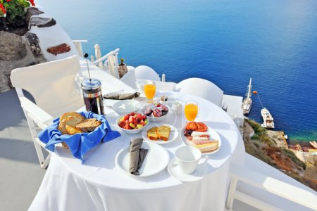 Photo for Breakfast on a terrace overlooking the sea in Oia, Santorini, Cyclades, Greece - Royalty Free Image