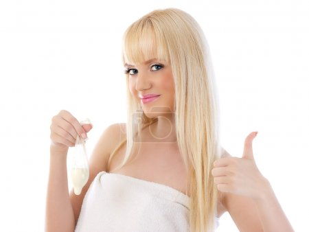 Pretty woman holding condom and giving thumbs up