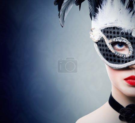 Beautiful girl in black carnival mask