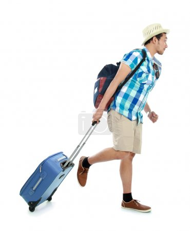 Photo for Portrait of a tourist walking with suitcase isolated on white background - Royalty Free Image
