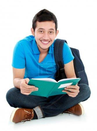 Foto de Feliz estudiante universitario sonriente sentado en el suelo leyendo un libro - Imagen libre de derechos